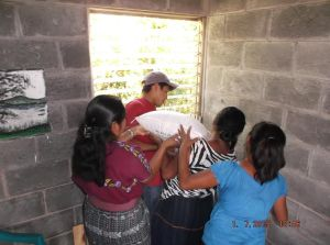 Marcos and Felipa with the help of local women inserting the 100 lb bags of sand.